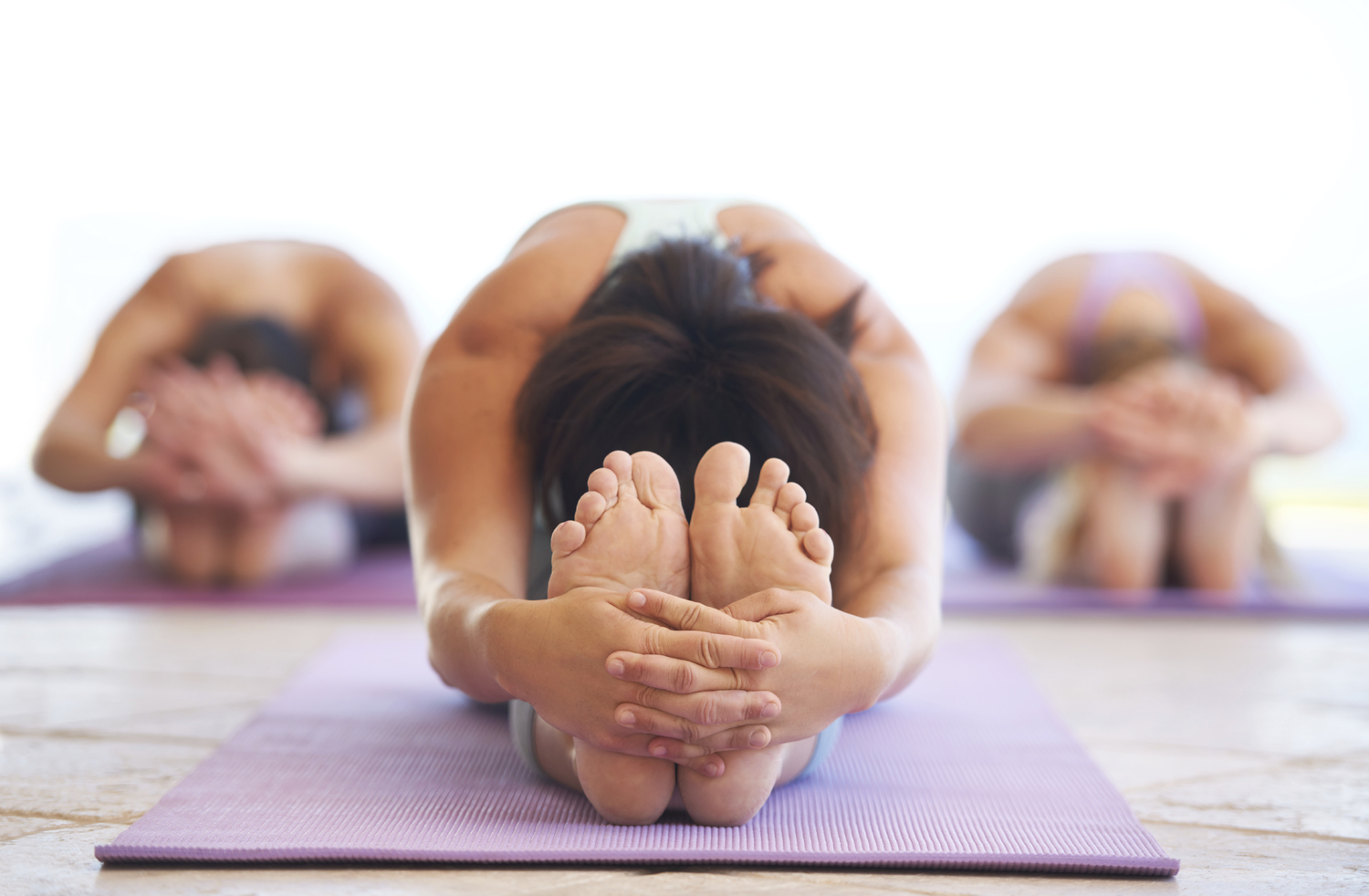 Young yoga instructor leading a class in stretching